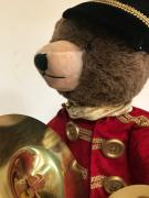Teddy bear with instrument cymbals.
