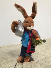 Rabbit with portable radio, picnic blanket and vegetable basket